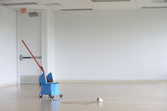 Golvmopp i hink på tomt rum Arkivfoto