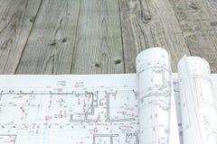 Golvplan med rullar av arkitektoniska ritningar på träskrivbordet Royaltyfri Bild