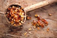 Goma arábiga, también conocida como goma arábiga - en cuchara de madera vieja Foto de archivo libre de regalías