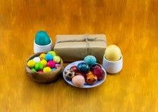 Goma colorida dos ovos da páscoa e um presente em um fundo de madeira foto de stock royalty free