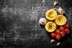 Goma cruda de los tallarines con ajo y tomates fotos de archivo