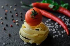 Goma cruda del fettuccine con la sal y los granos de pimienta gruesos del mar del chile del tomate fotos de archivo