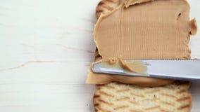Goma de la mantequilla de cacahuete con un cuchillo almacen de video