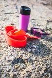 Goma gimnástica, taza terma y vidrios en la arena Imagen de archivo libre de regalías