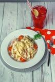 Goma italiana fragante de un fettuchina con tocino y queso con la ensalada de fruta fotografía de archivo libre de regalías