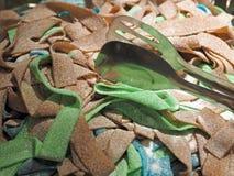 Gomas agridulces con los alicates de una comida foto de archivo