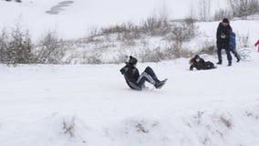 GOMEL, ΛΕΥΚΟΡΩΣΊΑ - 1 ΔΕΚΕΜΒΡΊΟΥ 2018: Χειμερινή διασκέδαση Τα παιδιά με τους γονείς πηγαίνουν σε έναν λόφο χιονιού απόθεμα βίντεο