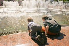 GOMEL, БЕЛАРУСЬ - 14-ое мая 2017: Игра детей с водой около фонтана города в городе Gomel Стоковые Изображения