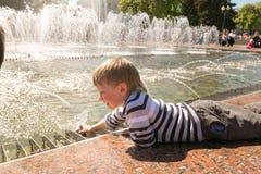 GOMEL, БЕЛАРУСЬ - 14-ое мая 2017: Игра детей с водой около фонтана города в городе Gomel Стоковые Изображения RF