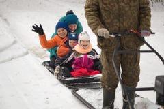 GOMEL, БЕЛАРУСЬ - 15-ОЕ ЯНВАРЯ 2017: Потеха зимы Снегоход звероловства семьи sledging Стоковая Фотография