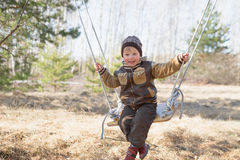 Gomel, Belarus - April 3, 2016: Family in a forest glade ride on  swing. Royalty Free Stock Photo