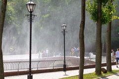 Gomel, Belarus - August 24, 2013: strangers walk by the fountain in the summer shady park. Gomel, Belarus - August 24, 2013: strangers walk by the fountain in Royalty Free Stock Photos