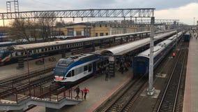 Gomel, Belarus - 18 avril 2018 : Les gens embarquant sur le train sur la plate-forme de station Trains et bâtiment de gare ferrov clips vidéos