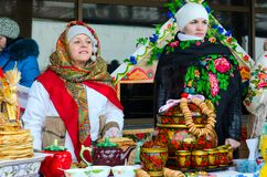 Two women are at table with pancakes and painted utensils during Shrovetide festivities. GOMEL, BELARUS - FEBRUARY 18, 2018: Two women are at table with pancakes Royalty Free Stock Images