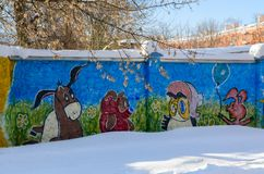 Graffiti depicting heroes of cartoon Winnie the Pooh on concrete fence in city courtyard, Gomel, Belarus. GOMEL, BELARUS - MARCH 5, 2018: Graffiti depicting Stock Photography