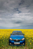 GOMEL, BELARUS - May 24, 2017: the blue car is parked on the rapeseed field. Stock Images