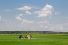 Gomel, Belarus - May 4, 2016: Tractor spraying wheat field with sprayer, herbicides and pesticides royalty free stock images