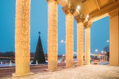 Gomel, Belarus. View Of Xmas Christmas Tree Through Column Of Go. Mel Regional Drama Theatre On Lenin Square At Evening Or Night Illuminations Lights. Famous stock image