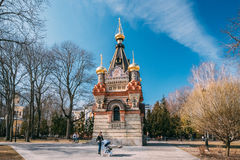 Gomel, Belarus. Young Woman With A Stroller Walking In City Park. Gomel, Belarus - March 8, 2017:  Young Woman With A Stroller Walking In City Park At Sunny Stock Photo