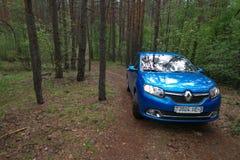GOMEL, BIAŁORUŚ - 24 2017 MAJ: RENO LOGAN błękitny samochód parkujący w ciemnym sosnowym lesie Zdjęcie Stock