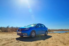 GOMEL, BIELORRÚSSIA - 7 de abril de 2018: Carro azul RENAULT LOGAN estacionado na borda da estrada fotografia de stock