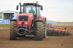 GOMEL, BIELORRÚSSIA - 19 DE ABRIL DE 2017: O trator de Bielorrússia cultiva um pedaço de terra Fotos de Stock Royalty Free