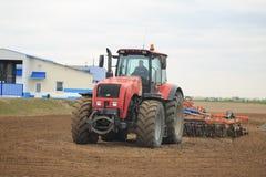 GOMEL, BIELORRÚSSIA - 19 DE ABRIL DE 2017: O trator de Bielorrússia cultiva um pedaço de terra Imagens de Stock
