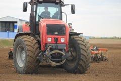 GOMEL, BIELORRÚSSIA - 19 DE ABRIL DE 2017: O trator de Bielorrússia cultiva um pedaço de terra Foto de Stock