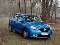 GOMEL, BIELORRÚSSIA - 10 DE ABRIL DE 2019: o carro azul de Renault Logan é estacionado na floresta fotos de stock