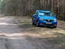 GOMEL, BIELORRÚSSIA - 10 DE ABRIL DE 2019: o carro azul de Renault Logan é estacionado na floresta imagens de stock royalty free