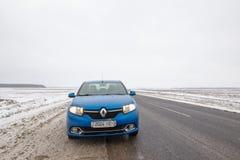 Gomel, Bielorrússia - 21 de fevereiro de 2017: Carro Renault - Logan na floresta do inverno com faróis fotos de stock