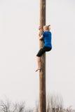 GOMEL, BIELORRÚSSIA - 21 de fevereiro de 2014: Escaladas da jovem mulher em um de madeira Fotografia de Stock Royalty Free