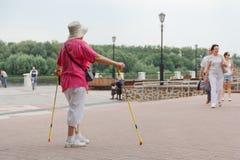 GOMEL, BIELORRÚSSIA - 25 de julho de 2018: uma mulher que faz esportes com varas escandinavas imagem de stock royalty free