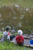 GOMEL, BIELORRÚSSIA - 25 de junho de 2017: Crianças da vila que pescam no lago com varas de pesca Foto de Stock Royalty Free