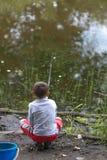 GOMEL, BIELORRÚSSIA - 25 de junho de 2017: Crianças da vila que pescam no lago com varas de pesca Fotos de Stock Royalty Free