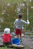 GOMEL, BIELORRÚSSIA - 25 de junho de 2017: Crianças da vila que pescam no lago com varas de pesca Imagens de Stock Royalty Free