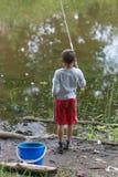 GOMEL, BIELORRÚSSIA - 25 de junho de 2017: Crianças da vila que pescam no lago com varas de pesca Fotografia de Stock Royalty Free