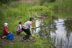 GOMEL, BIELORRÚSSIA - 25 de junho de 2017: Crianças da vila que pescam no lago com varas de pesca Imagem de Stock Royalty Free