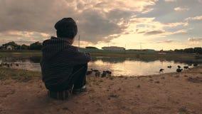 Gomel, Bielorrússia - 25 de junho de 2018: os povos na água alimentam patos selvagens filme