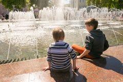 GOMEL, BIELORRÚSSIA - 14 de maio de 2017: Jogo de crianças com água perto de uma fonte da cidade na cidade de Gomel Fotos de Stock