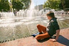 GOMEL, BIELORRÚSSIA - 14 de maio de 2017: Jogo de crianças com água perto de uma fonte da cidade na cidade de Gomel Fotografia de Stock Royalty Free
