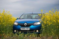 GOMEL, BIELORRÚSSIA - 24 de maio de 2017: o carro azul é estacionado no campo da colza Imagem de Stock