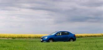 GOMEL, BIELORRÚSSIA - 24 de maio de 2017: o carro azul é estacionado no campo verde Imagens de Stock Royalty Free