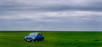 GOMEL, BIELORRÚSSIA - 24 de maio de 2017: o carro azul é estacionado no campo verde Fotos de Stock Royalty Free