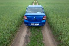 GOMEL, BIELORRÚSSIA - 24 de maio de 2017: O carro azul de RENO LOGAN é estacionado no campo verde Fotografia de Stock