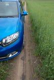 GOMEL, BIELORRÚSSIA - 24 de maio de 2017: O carro azul de RENO LOGAN é estacionado no campo verde Imagens de Stock