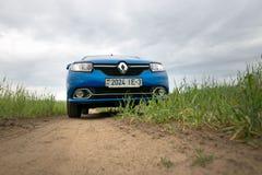 GOMEL, BIELORRÚSSIA - 24 de maio de 2017: O carro azul de RENO LOGAN é estacionado no campo verde Foto de Stock