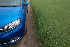 GOMEL, BIELORRÚSSIA - 24 de maio de 2017: O carro azul de RENO LOGAN é estacionado no campo verde Fotos de Stock Royalty Free