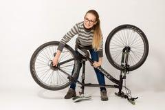 GOMEL, BIELORRÚSSIA - 12 de maio de 2017: TRILHA do Mountain bike em um fundo branco A menina está montando Imagens de Stock