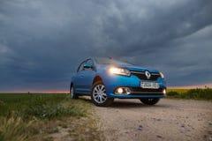 GOMEL, BIELORRÚSSIA - 15 de maio de 2018: O carro azul de RENO LOGAN estacionou no campo contra um céu tormentoso imagem de stock